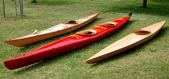 Three wooden kayaks on the lawn